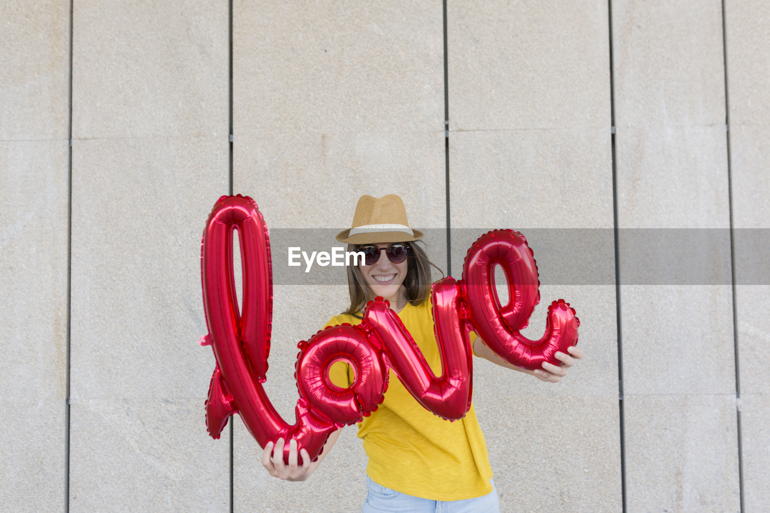 Portrait of woman holding balloons with text while standing against wall