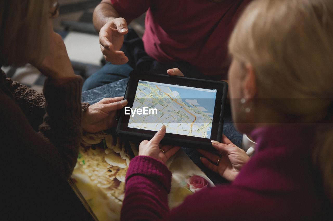 People looking at map on digital tablet