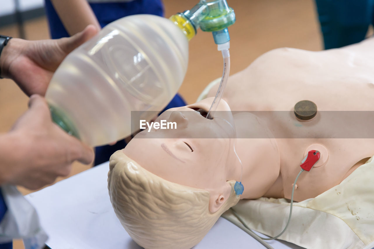 Midsection Of Paramedics Practicing With Dummy At Hospital