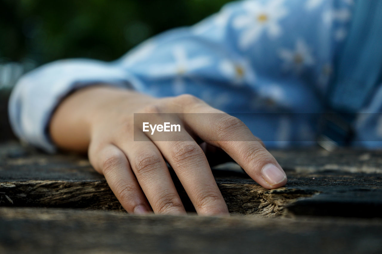 Cropped hand of woman on wooden table