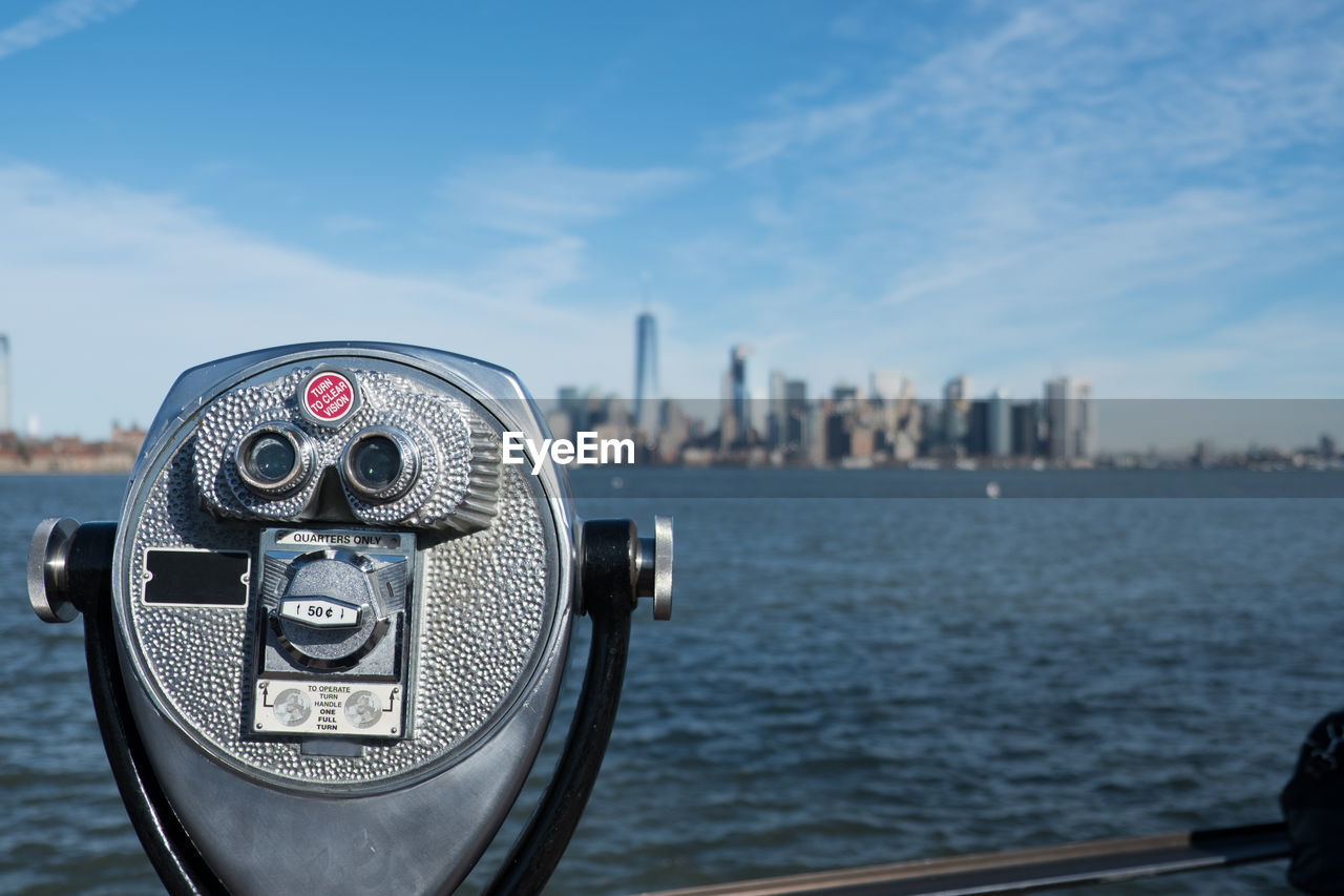 binoculars, coin operated, sky, coin-operated binoculars, water, building exterior, architecture, city, focus on foreground, built structure, nature, surveillance, day, close-up, cityscape, no people, tourism, sea, travel destinations, outdoors, skyscraper, office building exterior, hand-held telescope