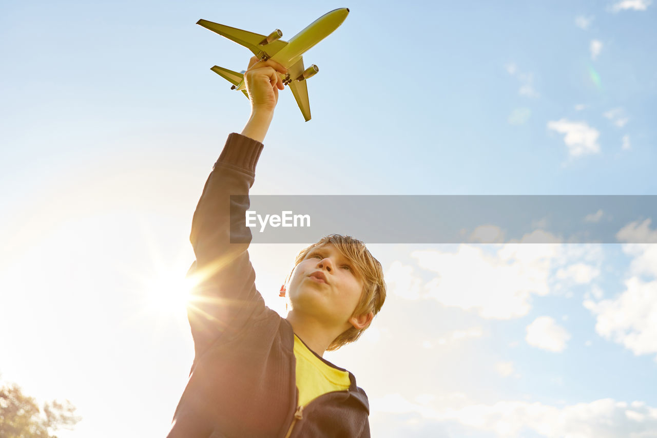 LOW ANGLE VIEW OF BOY WITH ARMS OUTSTRETCHED AGAINST SKY