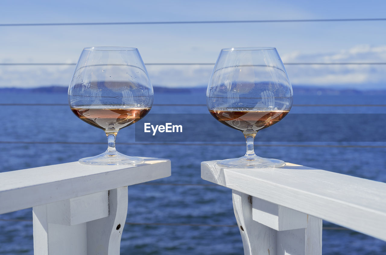 Close-up of brandy snifters on white adirondack chairs against sea