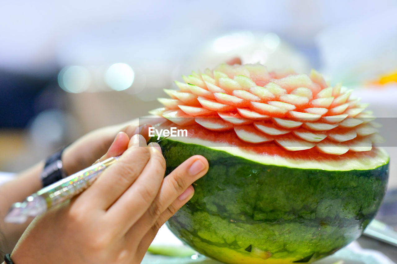 human hand, food and drink, hand, food, freshness, human body part, healthy eating, one person, real people, fruit, holding, wellbeing, focus on foreground, close-up, unrecognizable person, lifestyles, finger, slice, human finger, body part, temptation