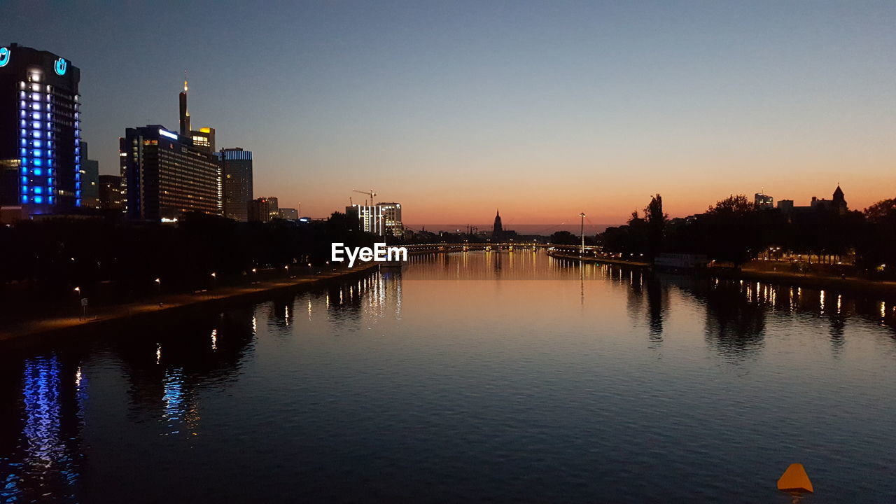 architecture, building exterior, sunset, skyscraper, built structure, city, reflection, cityscape, water, river, urban skyline, travel destinations, waterfront, city life, outdoors, illuminated, modern, sky, no people, clear sky, tree, nature
