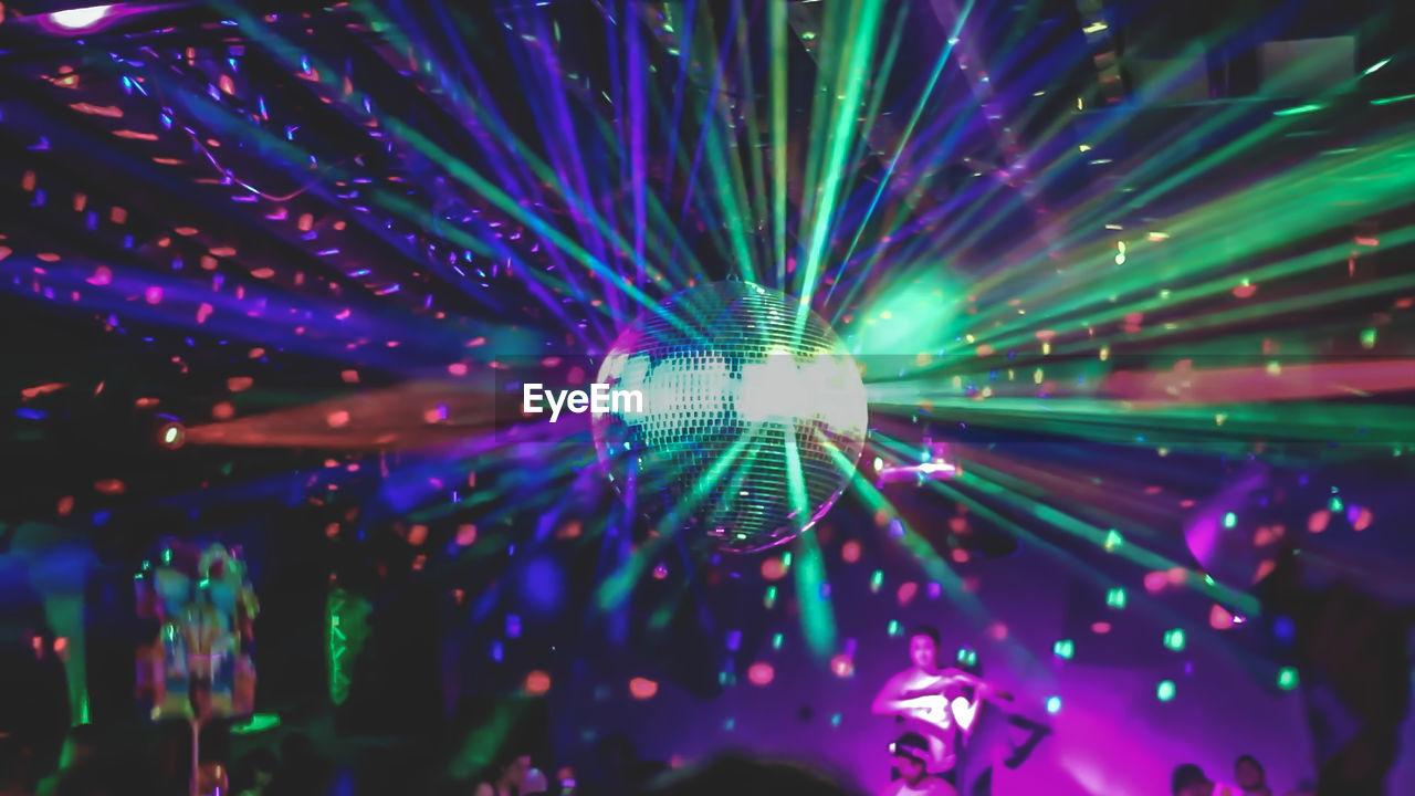 People Enjoying Below Illuminated Disco Ball At Nightclub