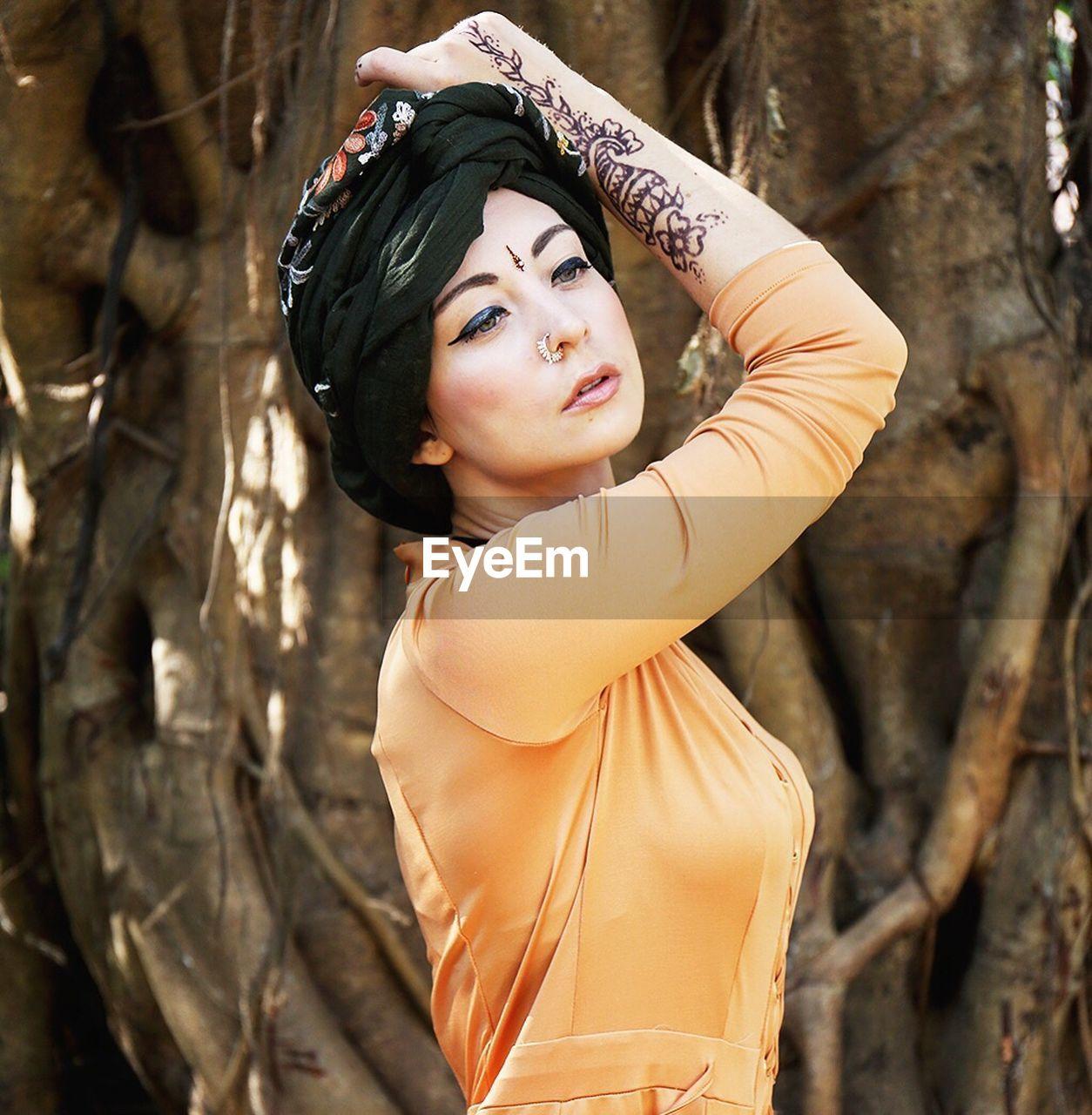 Beautiful fashion model posing against tree trunk