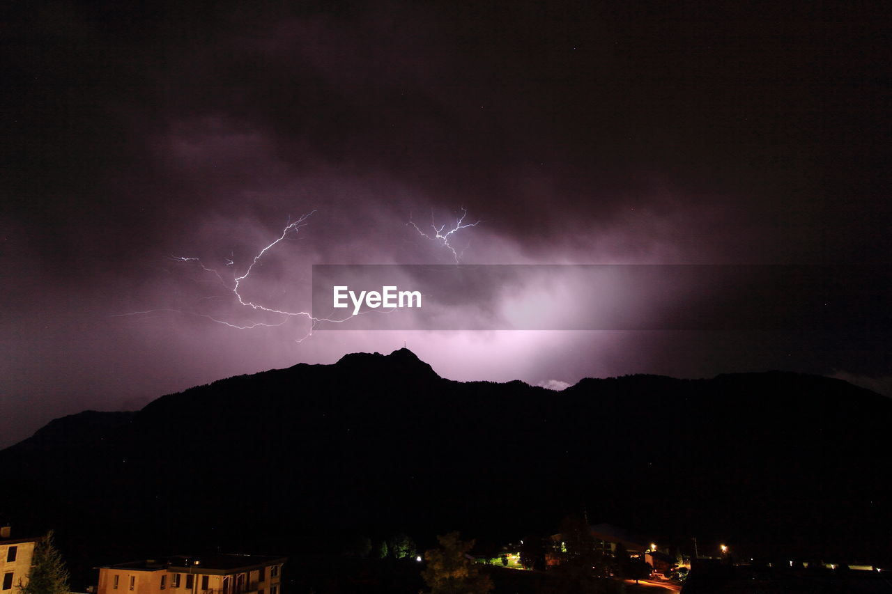 Lightning Over Silhouette Mountains Against Sky At Night