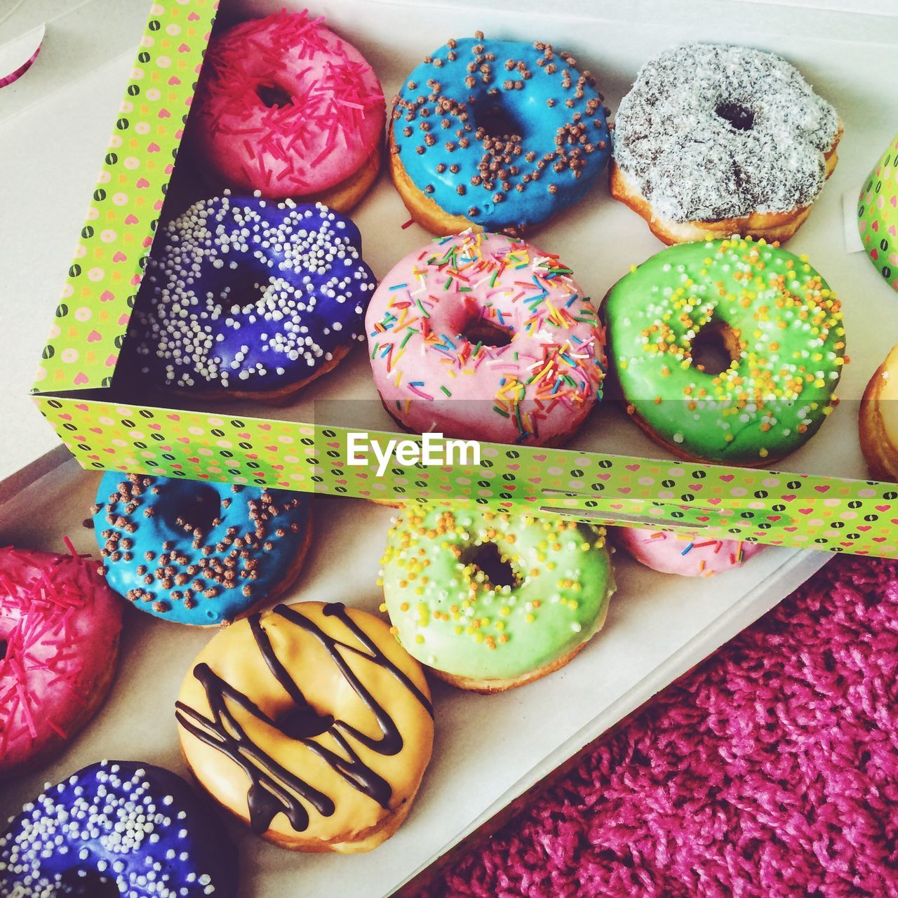 High angle view of donuts in cardboard boxes on rug