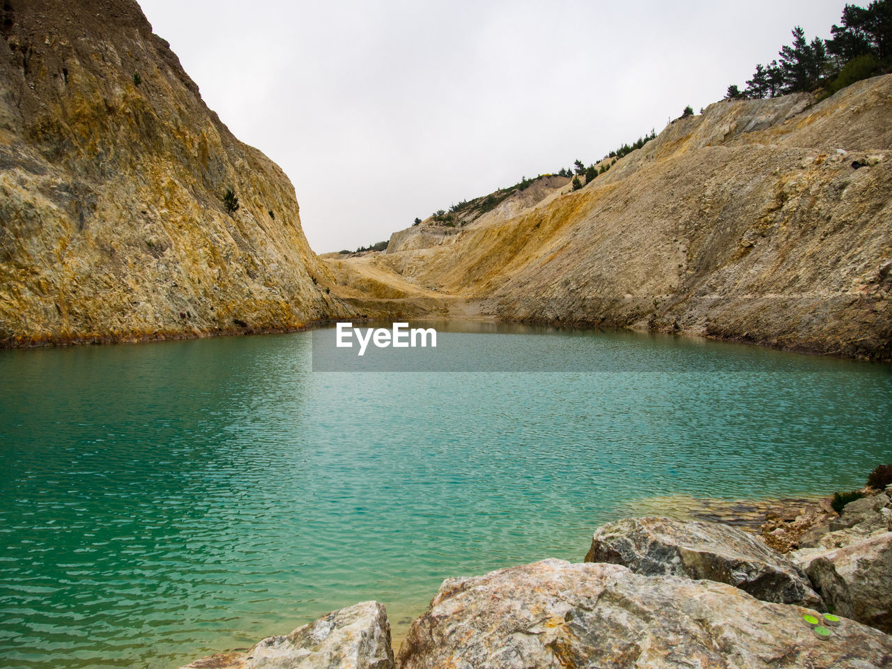 water, rock, rock - object, scenics - nature, solid, tranquility, tranquil scene, beauty in nature, sky, no people, mountain, nature, day, lake, non-urban scene, rock formation, idyllic, remote, outdoors, turquoise colored, formation