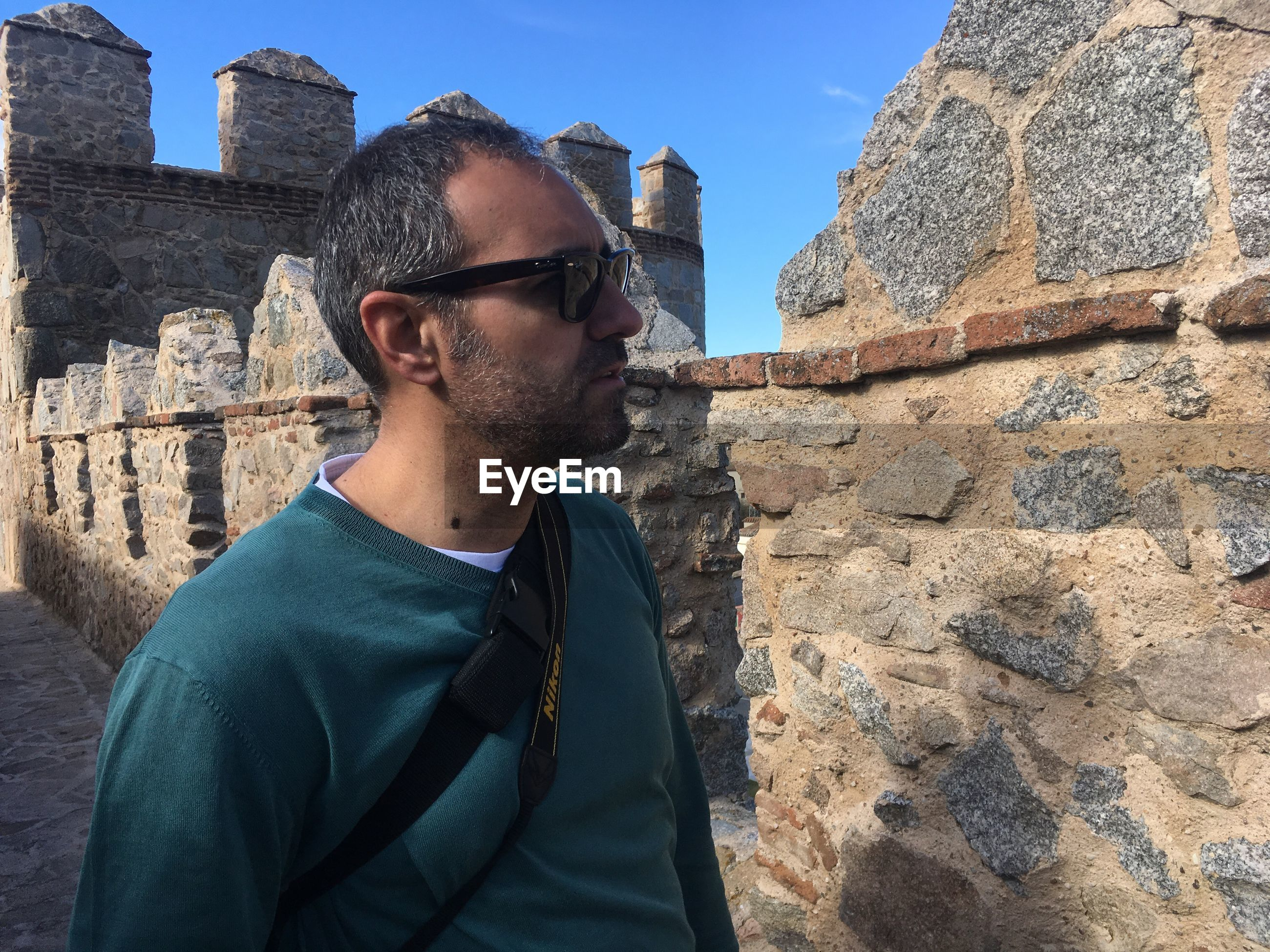 Side view of man wearing sunglasses by fort