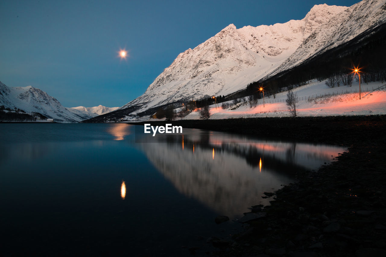 Scenic view of lake by snowcapped mountains against sky at dusk