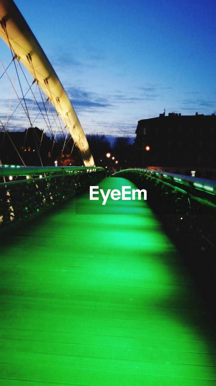 Illuminated green footbridge at night