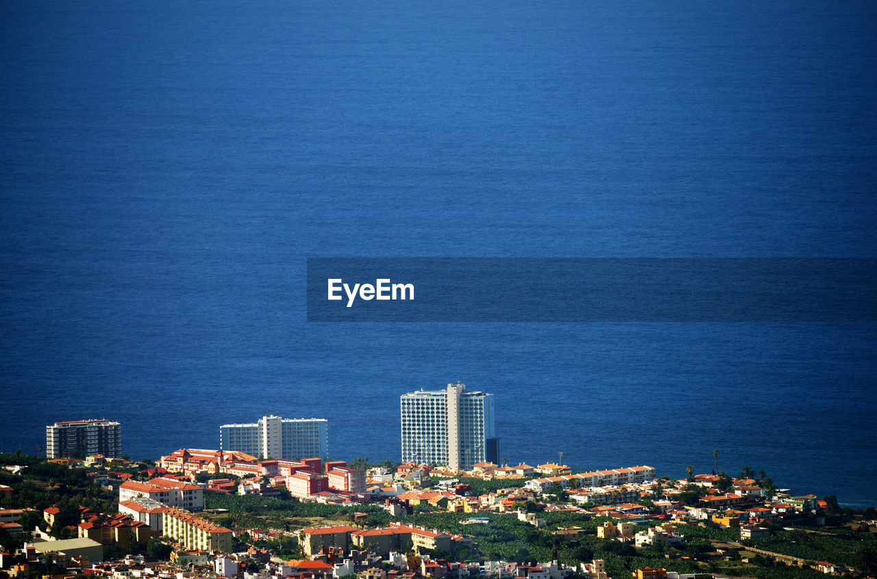 High Angle Shot Of Townscape Against Blue Sea