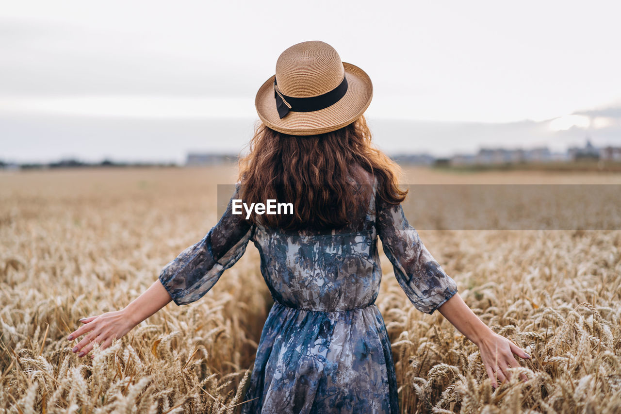 Rear view of woman wearing hat standing amidst crops in farm
