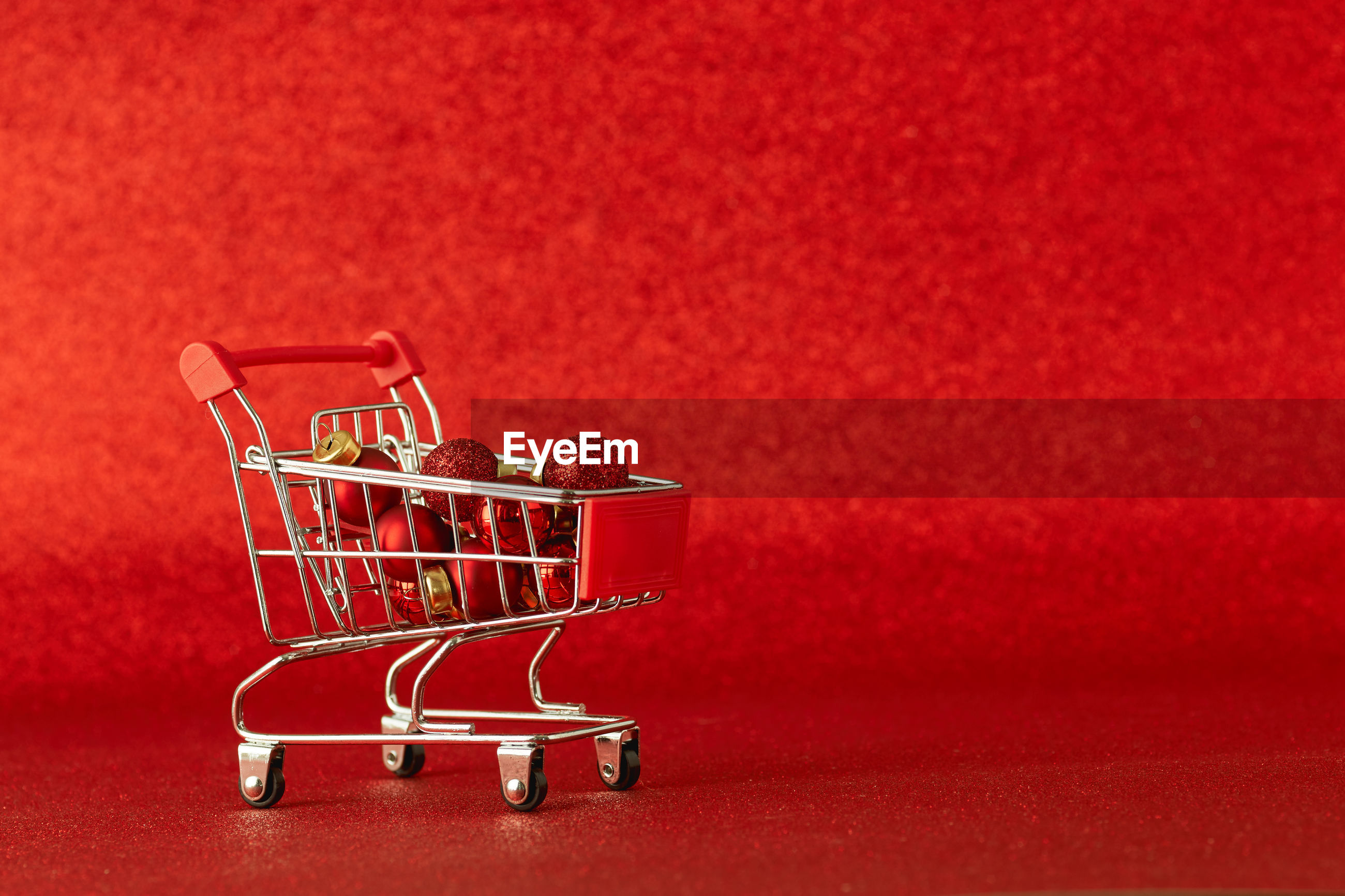 Christmas ornaments in shopping cart on red background