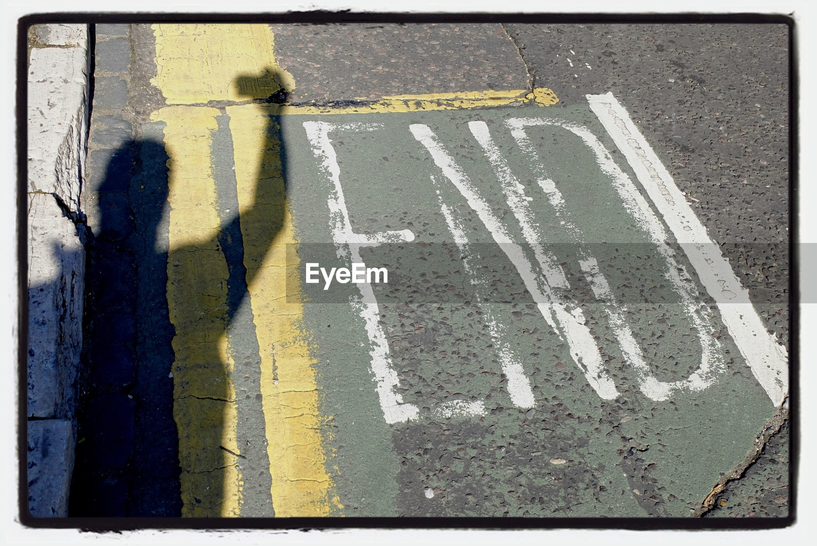 transfer print, road marking, street, road, high angle view, asphalt, auto post production filter, communication, shadow, focus on shadow, men, lifestyles, unrecognizable person, human representation, standing, transportation, guidance, day