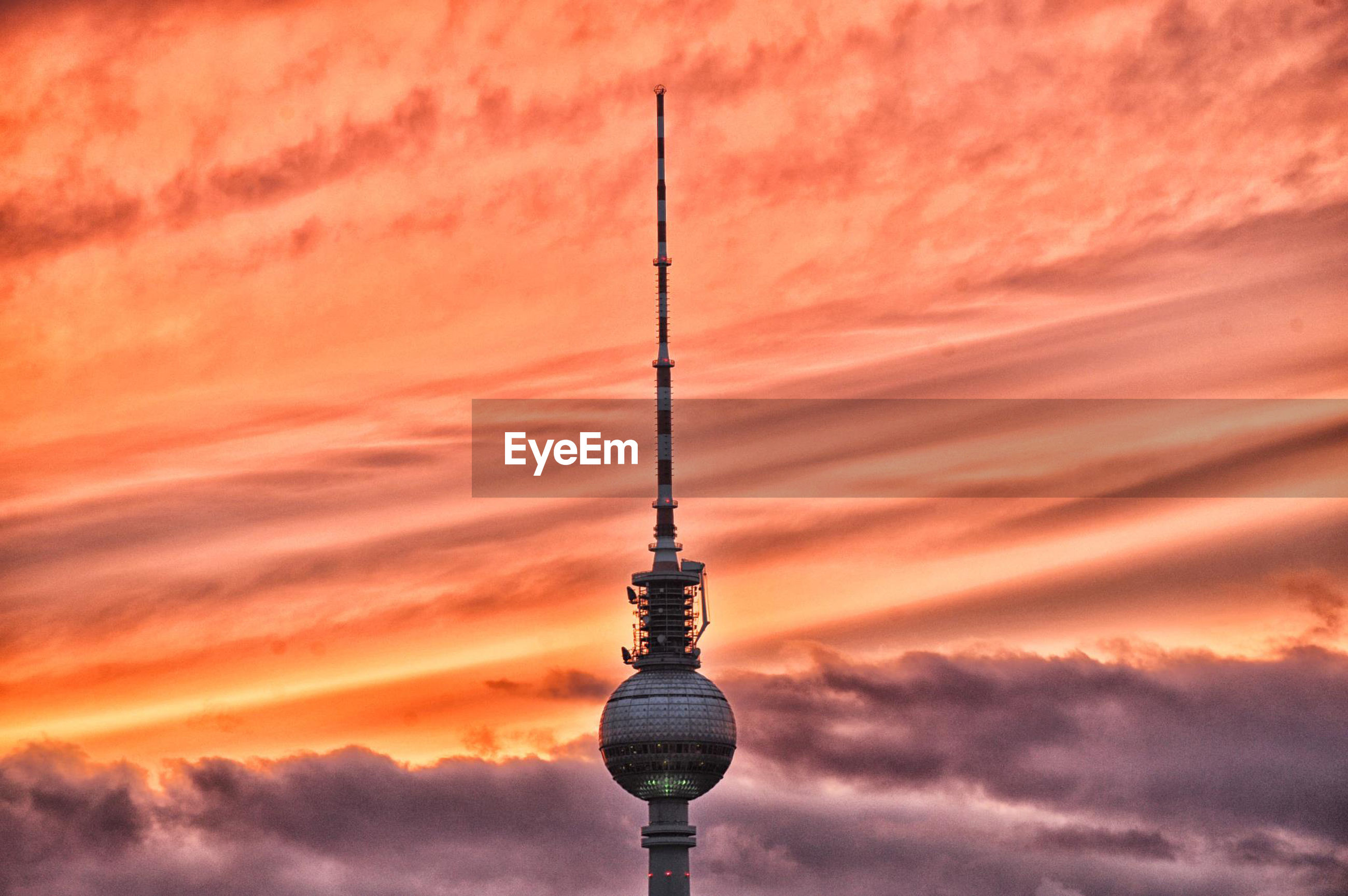 Low angle view of fernsehturm against cloudy sky during sunset