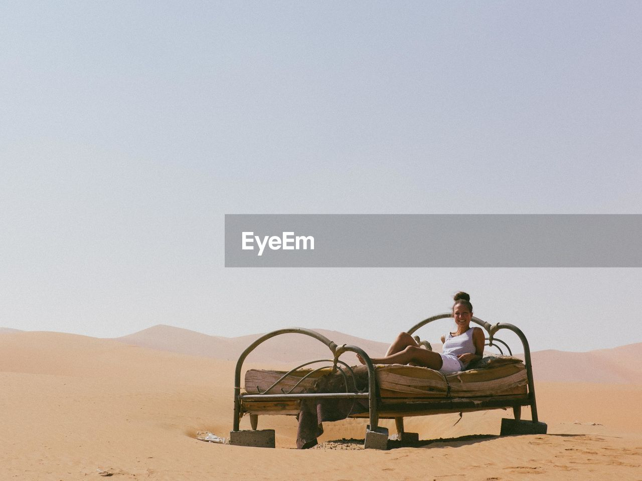 Woman Lying On Old Bed In Desert
