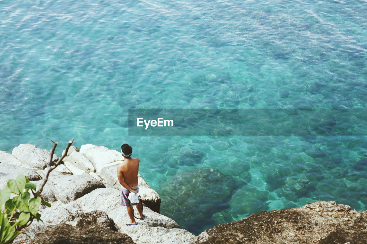 High angle view of shirtless man standing on rock at seaside