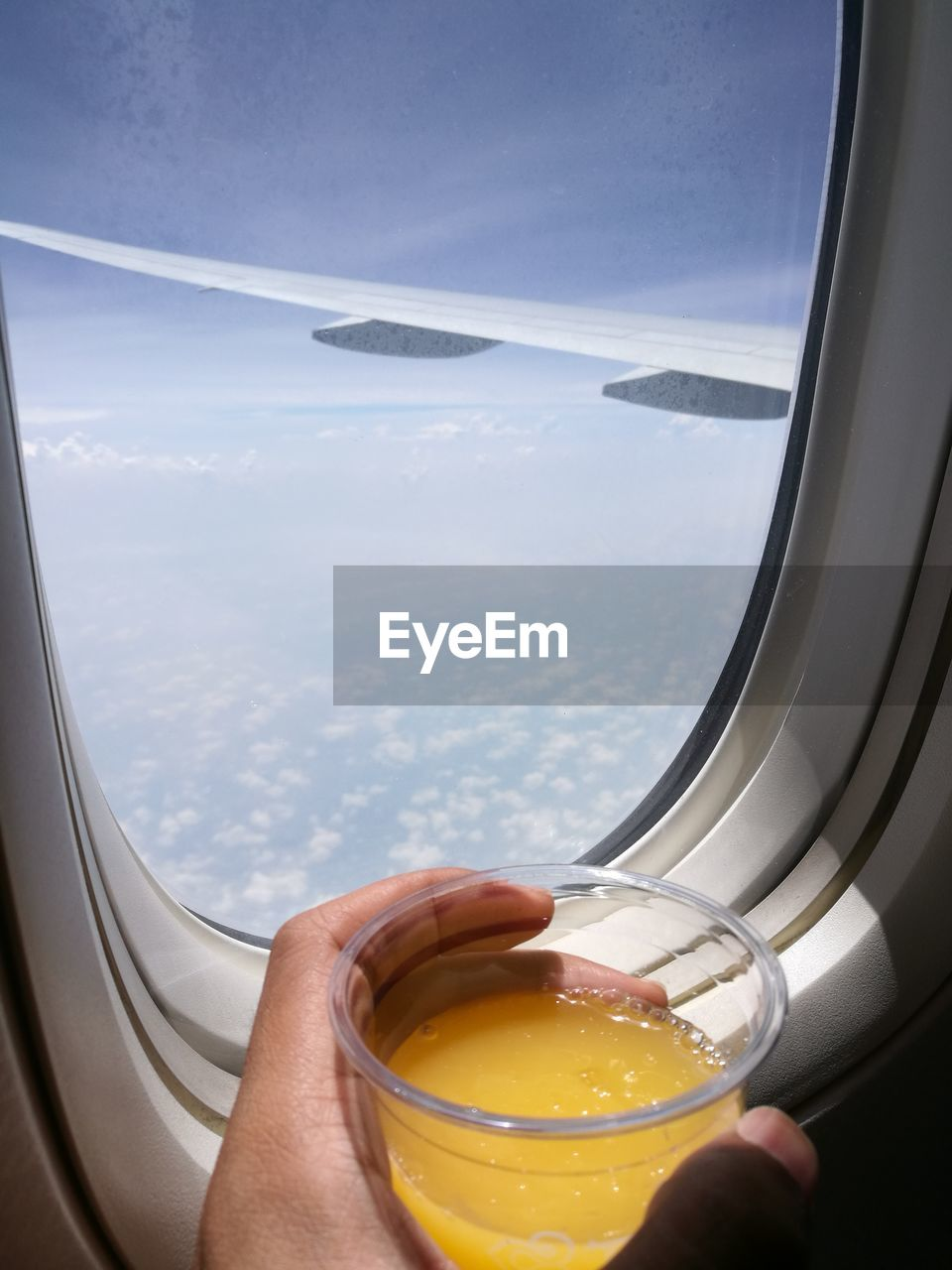 Cropped Hand Of Person Holding Juice By Airplane Window