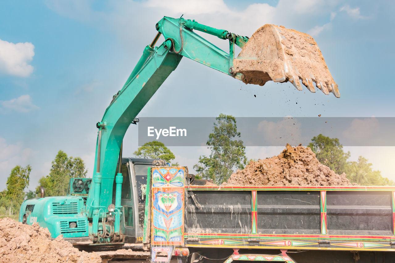 Bulldozer on land against sky