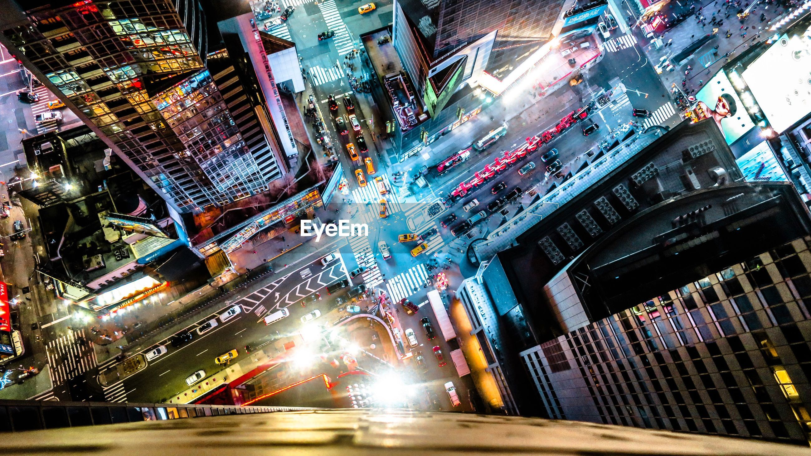 High angle view of illuminated city street amidst buildings at night