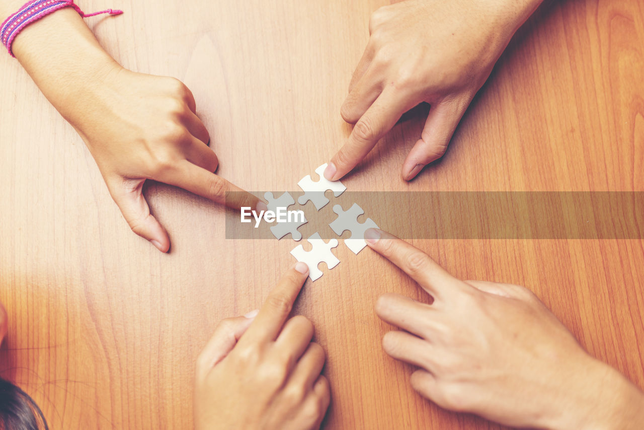 human hand, hand, real people, human body part, leisure activity, indoors, high angle view, togetherness, holding, women, adult, group of people, lifestyles, men, people, jigsaw piece, jigsaw puzzle, table, body part, finger