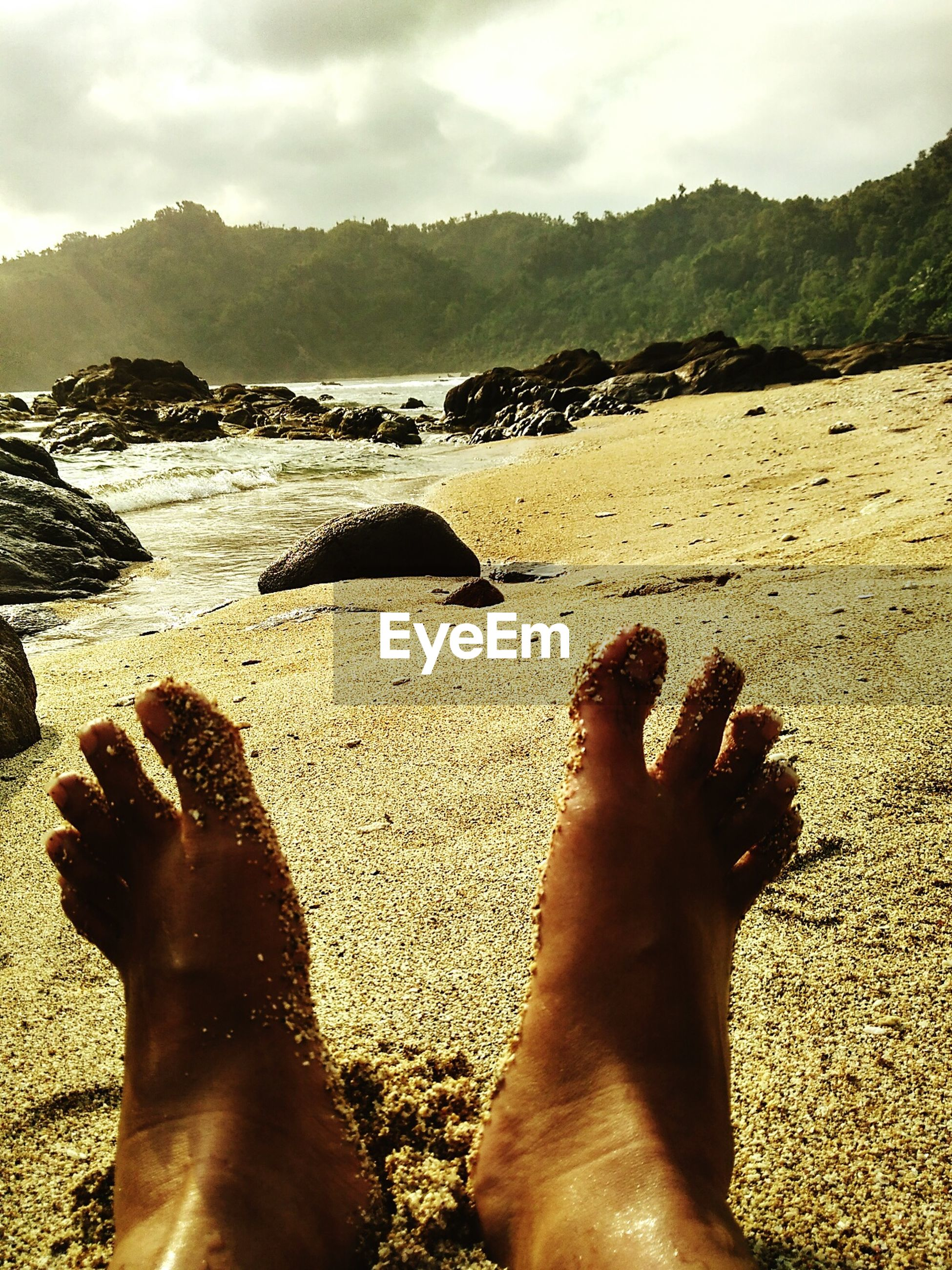 low section, beach, person, water, sand, personal perspective, barefoot, sea, lifestyles, leisure activity, shore, human foot, relaxation, sky, vacations, nature