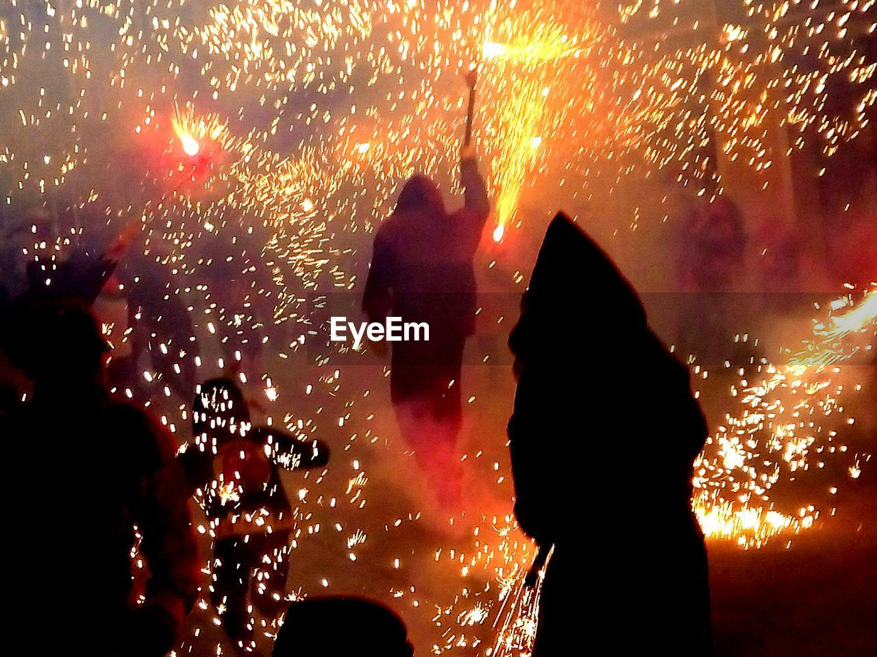 event, arts culture and entertainment, real people, night, celebration, women, silhouette, illuminated, lifestyles, motion, burning, men, orange color, glowing, people, standing, group of people, heat - temperature, nature, leisure activity, firework, outdoors, firework display, light, firework - man made object