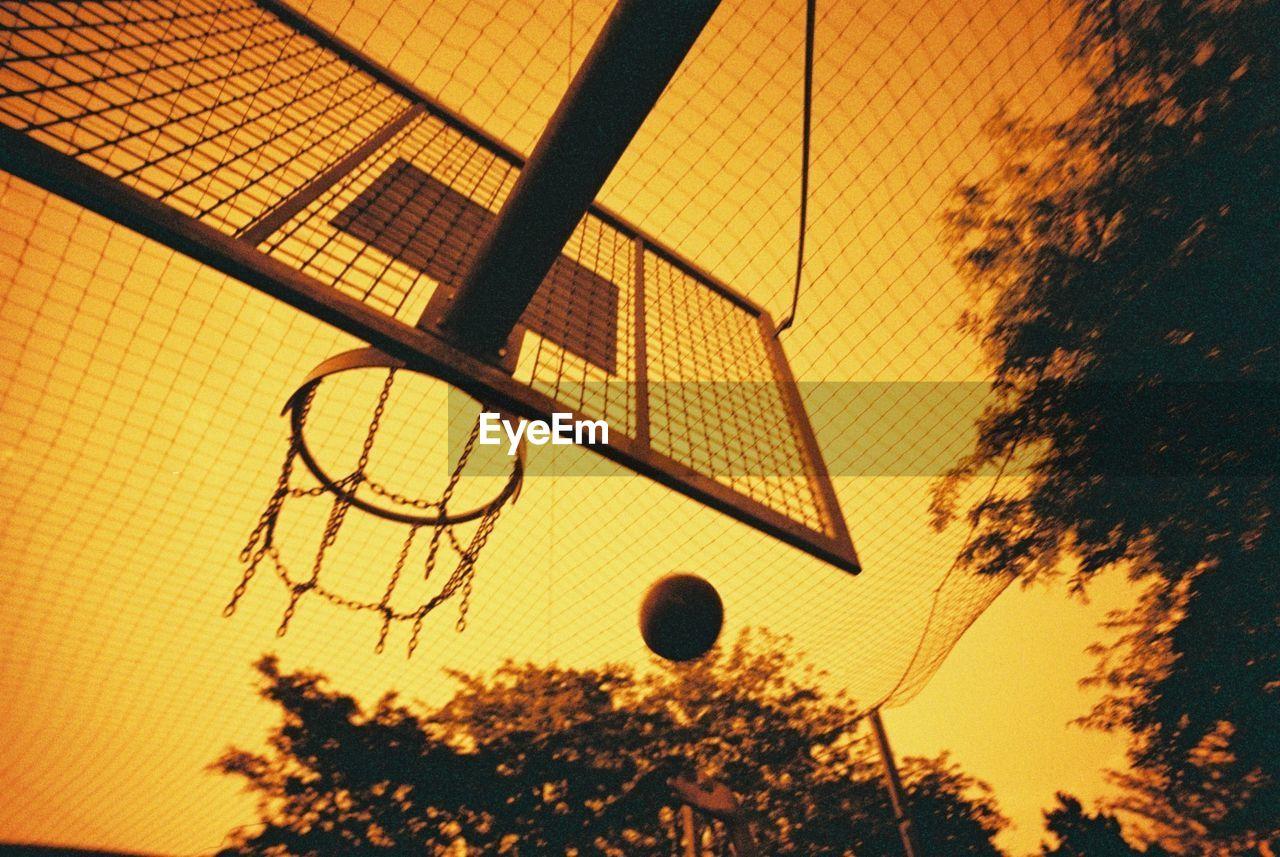 Basketball backboard and hoop on street in orange colors of sunset