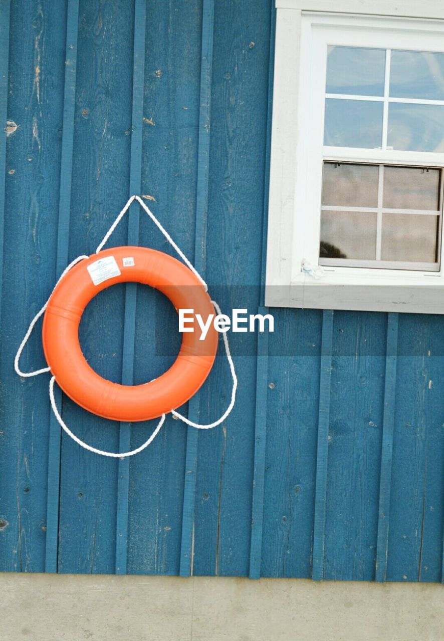 orange color, protection, safety, day, security, blue, wood - material, no people, life belt, built structure, architecture, geometric shape, circle, shape, building exterior, hanging, red, tubing, tube, outdoors, garden hose