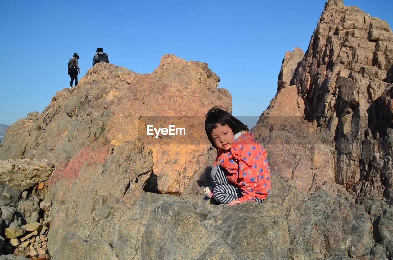 Side view of girl sitting on rock