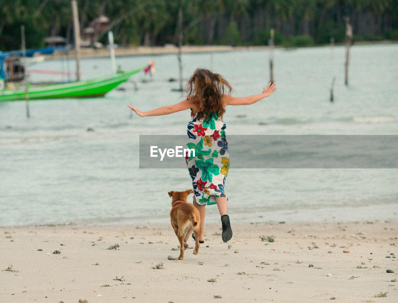 Rear View Of Woman Running With Dog At Beach At Ko Samui