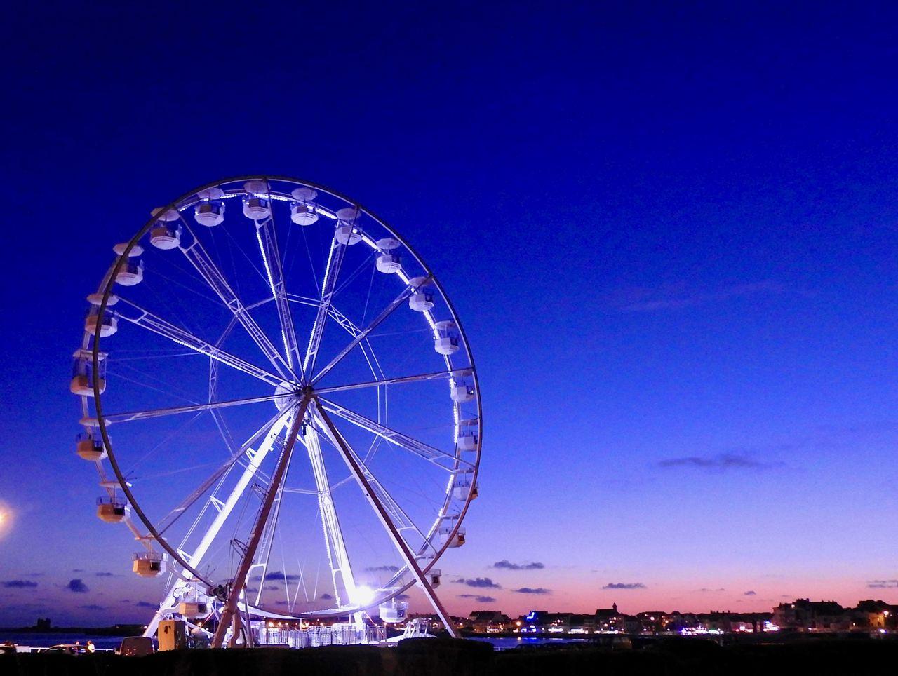 amusement park ride, amusement park, ferris wheel, sky, arts culture and entertainment, blue, nature, illuminated, architecture, no people, dusk, built structure, copy space, sunset, circle, clear sky, outdoors, shape, geometric shape, carnival, fairground