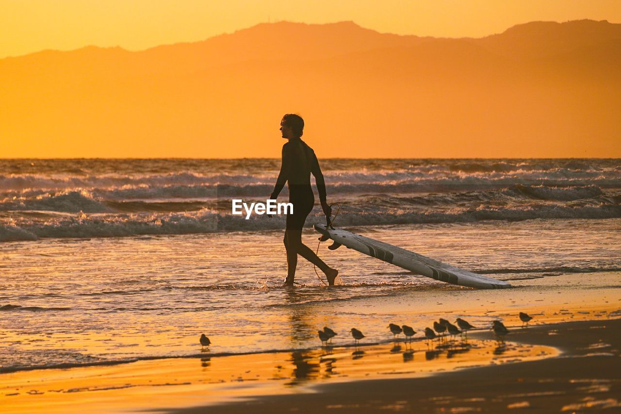 Full Length Of Man With Surfboard Walking On Beach At Sunset