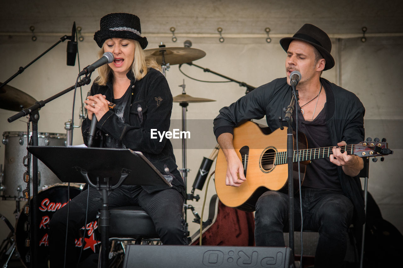two people, music, singing, playing, drum kit, musician, performance, young men, young adult, real people, musical instrument, microphone, arts culture and entertainment, singer, guitar, indoors, recording studio, performance group, skill, drummer, young women, electric guitar, plucking an instrument, rock group, day, people, adult