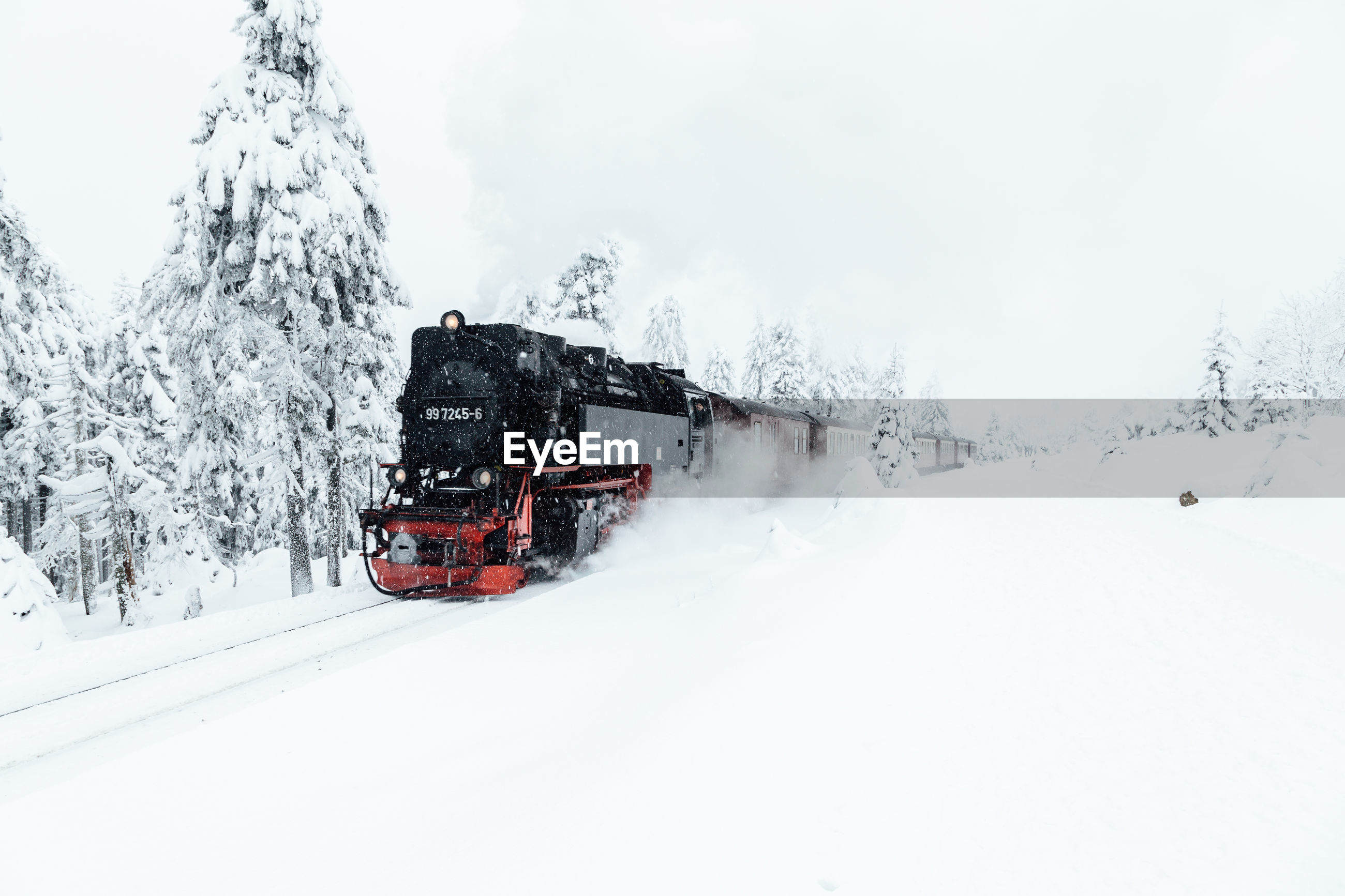 TRAIN ON SNOW COVERED RAILROAD TRACK AGAINST SKY
