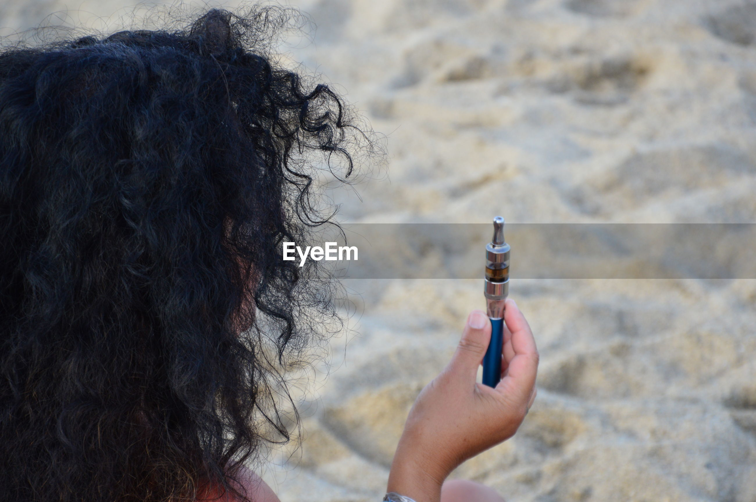 Rear view of woman holding electronic cigarette at beach