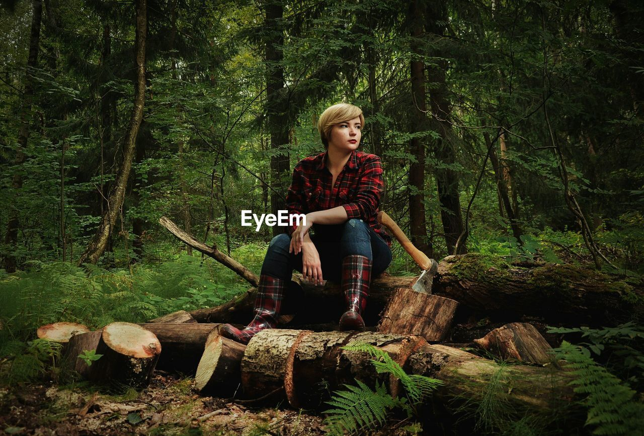 Young Woman Sitting On Tree Stump In Forest