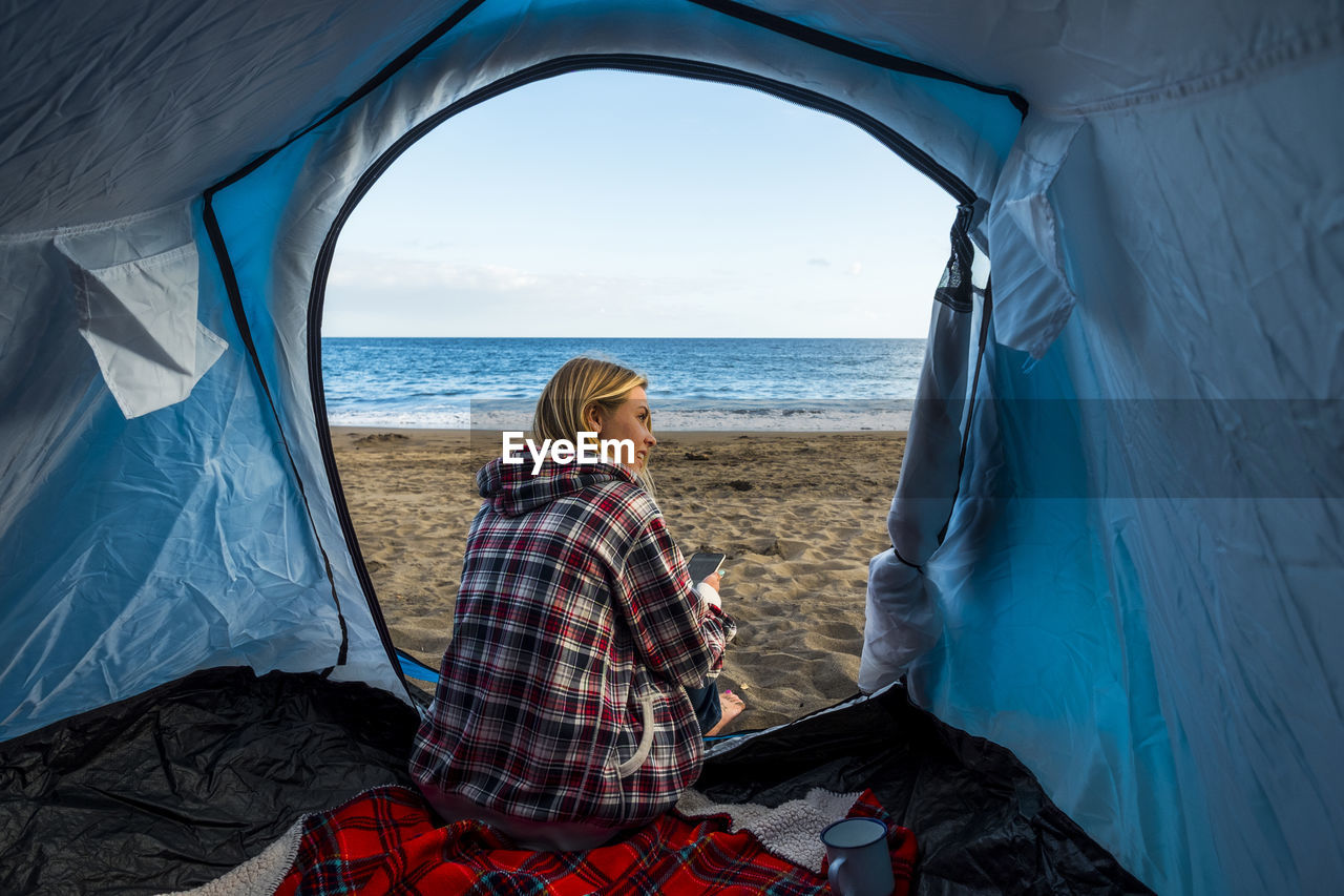 Rear View Of Woman Sitting In Tent At Beach