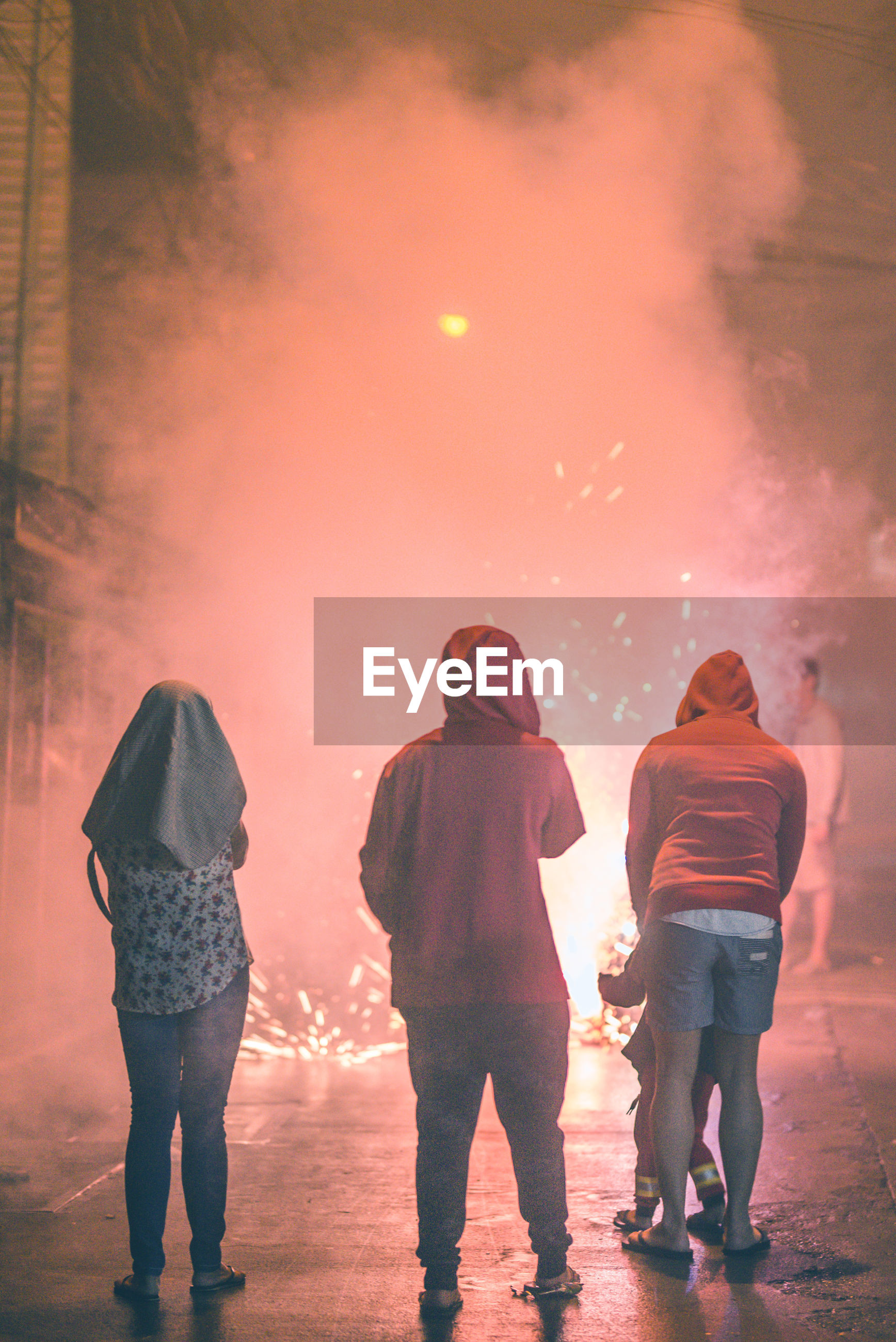 Rear view of people standing on street by firework at night