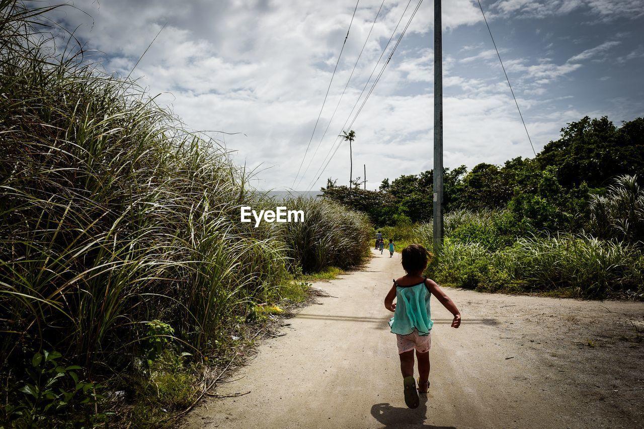 Full length of girl running on road against sky