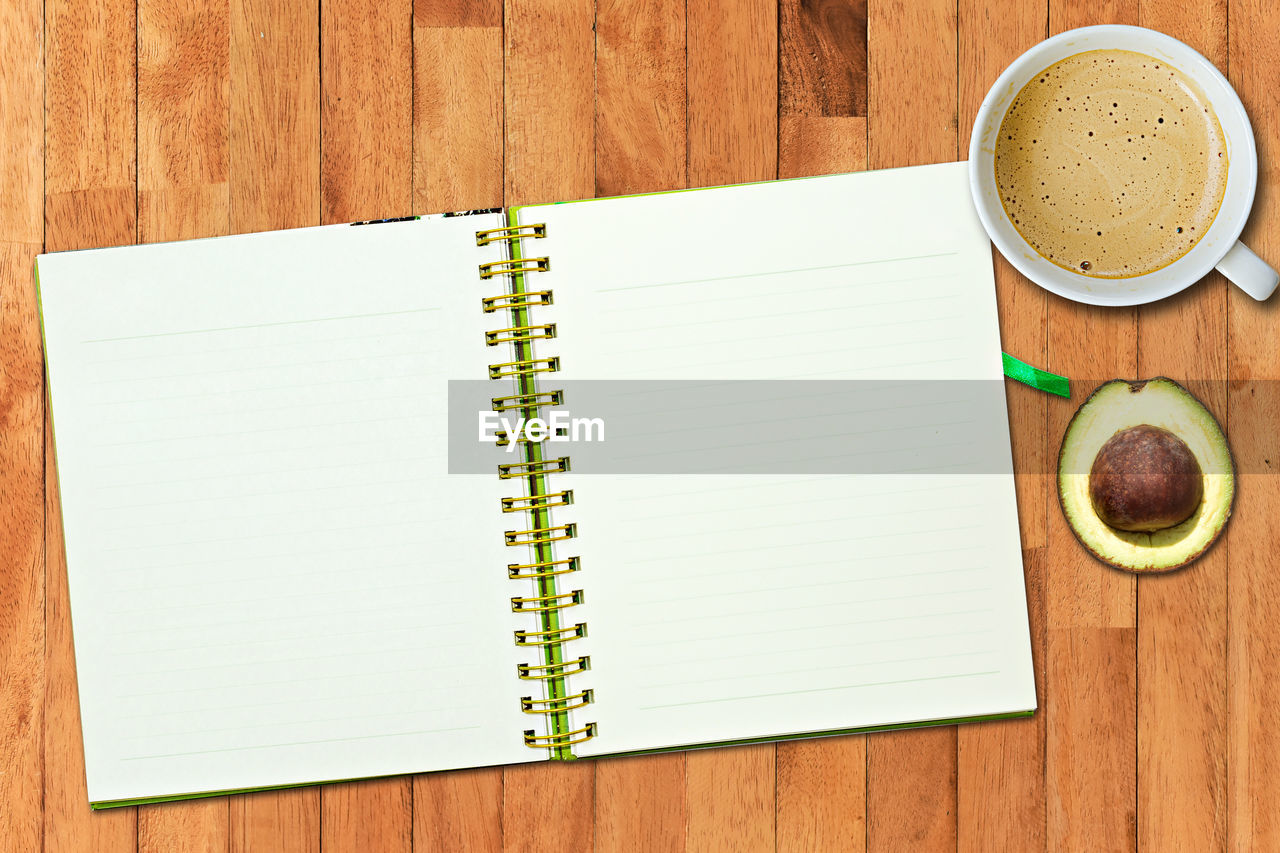 food and drink, table, wood - material, spiral notebook, directly above, drink, cup, still life, coffee - drink, coffee, indoors, book, coffee cup, mug, publication, note pad, food, no people, high angle view, refreshment, blank