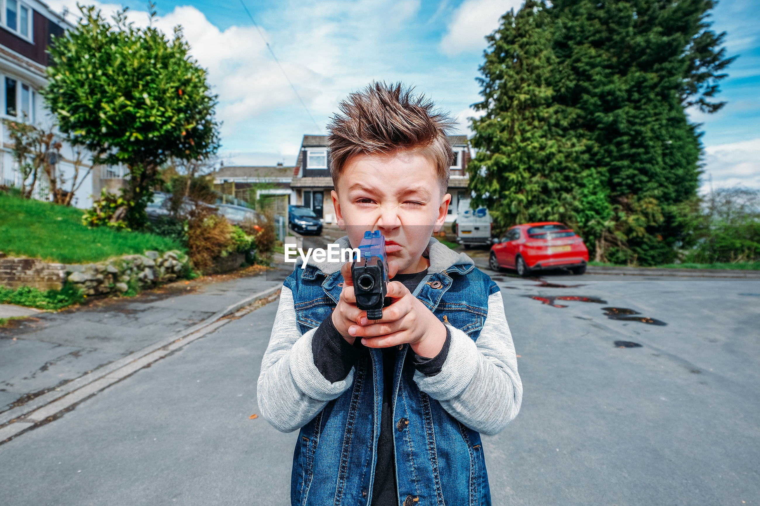 Portrait of boy shooting with toy handgun while standing on road