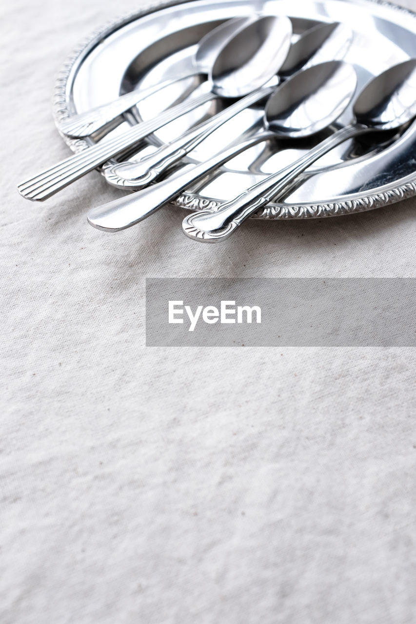 table, still life, eating utensil, kitchen utensil, indoors, metal, fork, close-up, no people, selective focus, spoon, table knife, silver colored, silver - metal, household equipment, knife, high angle view, silverware, tablecloth, copy space, steel, personal accessory
