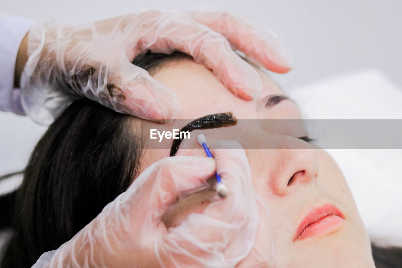 Cropped Hand Of Beautician Using Cotton Swab On Female Customer