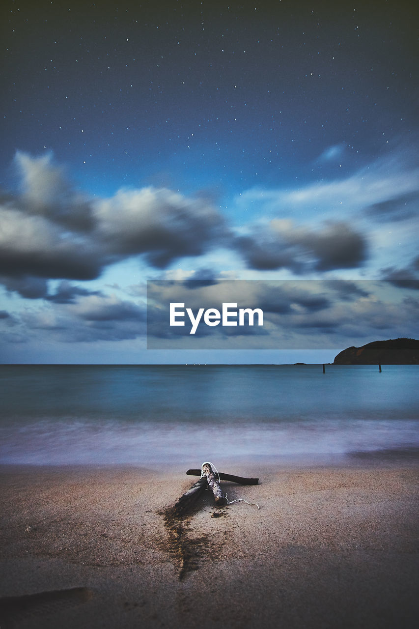 Scenic view of beach against cloudy sky at night