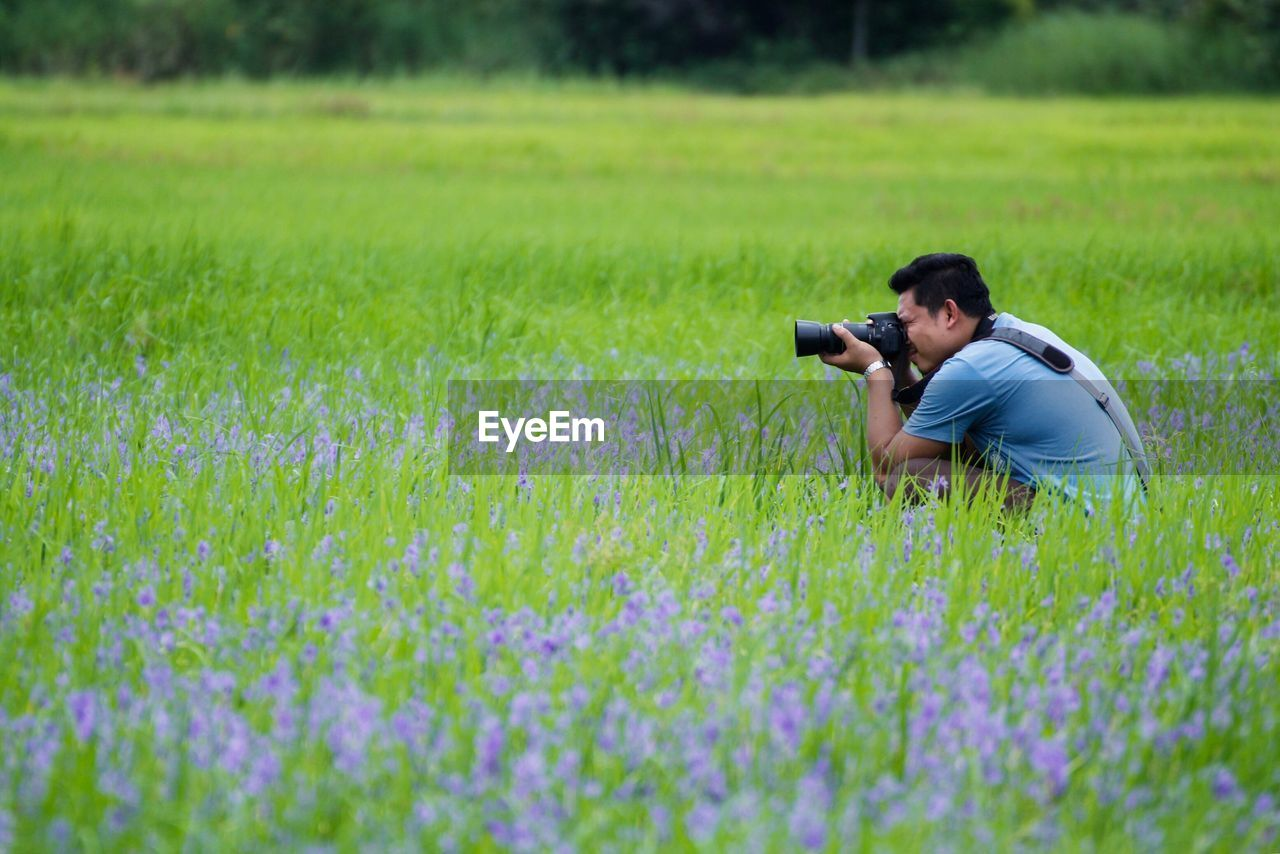Side View Of Man Photographing Through Camera While Crouching On Field