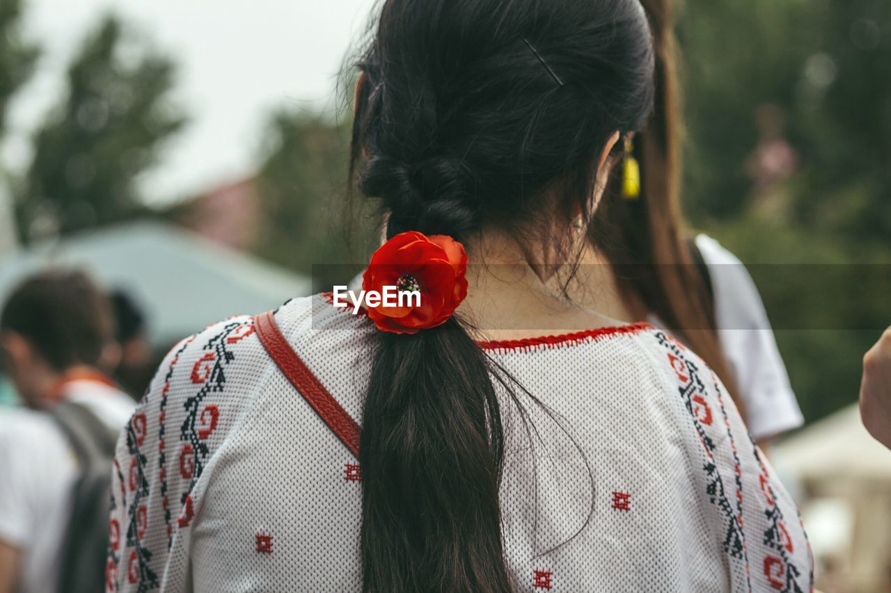 Rear View Of Woman Wearing Red Flower